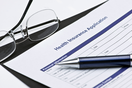 Health insurance application with glasses, and pen.