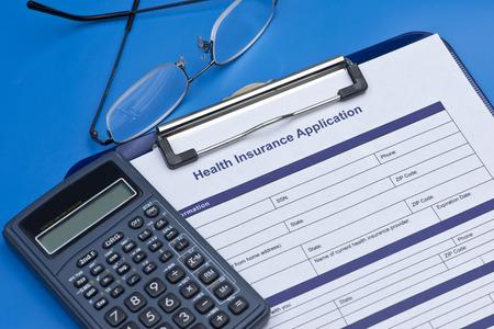 Health insurance application with glasses, and calculator. Zdjęcie Seryjne