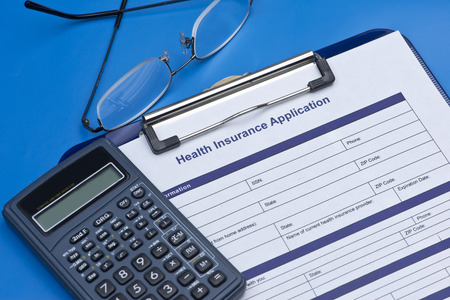 tax law: Health insurance application with glasses, and calculator. Stock Photo