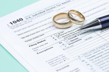 auditor�a: Anillos de bodas con el formulario de impuestos de Estados Unidos 1040 y la pluma.