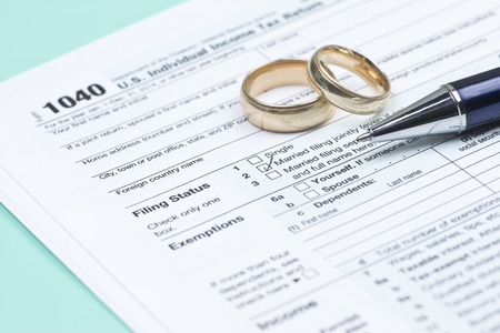 tax forms: Wedding rings with United States tax form 1040 and pen.