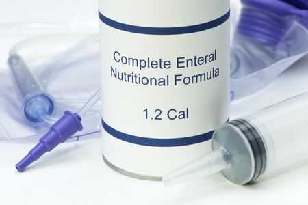 Close up view of feeding syringe and feeding bag with can of enteral formula.