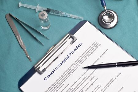 consent: Informed consent for surgical procedure form on surgical table. Stock Photo