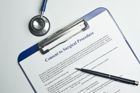 consent: Informed consent for surgical procedure form on white table with pen and stethoscope. Stock Photo