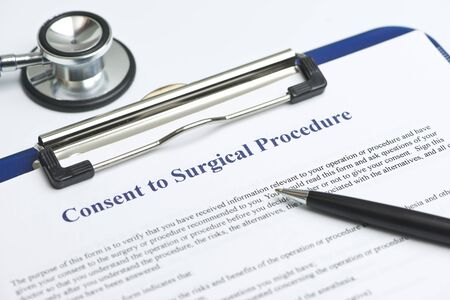 consent: Informed consent for surgical procedure form on white table with stethoscope. Stock Photo