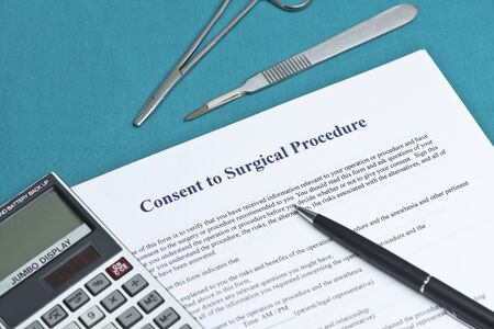 consent: Informed consent for surgical procedure form on surgical table with calculator and pen.