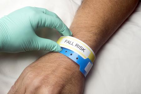 Verpleegkundige controleert ziekenhuispatiënt valrisico armband. Stockfoto