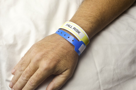 Hospital patient with fall risk bracelet on wrist. Reklamní fotografie