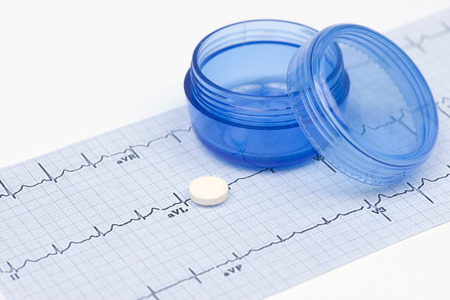 electrocardiograph: Daily aspirin tablet with electrocardiograph and blue pill container.