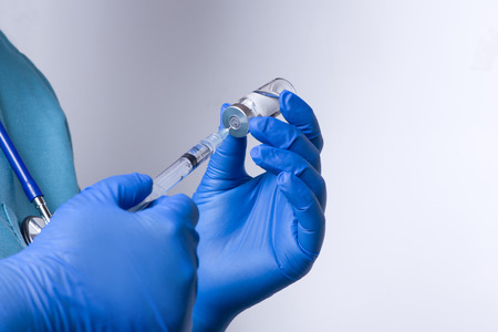 syringe injection: Nurse draws solution into syringe from vial in clinic office.