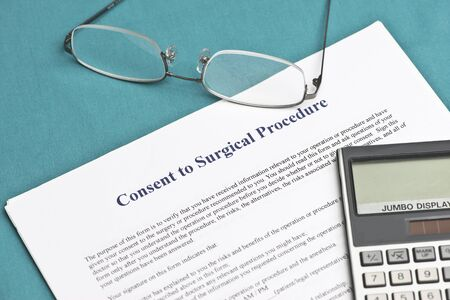 informed: Informed consent form with calculator and glasses.