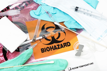 Biohazard waste bags with used syringes,  needles, bandages, and other medical waste. photo