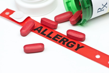 identifier: Allergy alert hospital wristband with medication and prescription bottle. Stock Photo