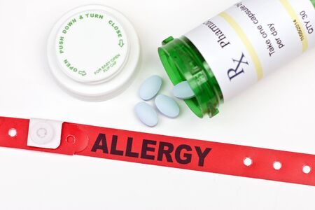 Allergy alert hospital wristband with medication and prescription bottle. Stock Photo