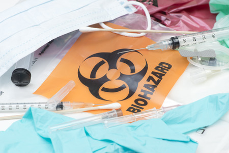 hazardous waste: Biohazard waste bags with used syringes,  needles, bandages, and other medical waste.