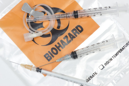 Biohazard waste bag with used syringes, and IV needles.
