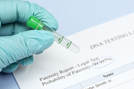 paternity: Lab technician holds culture tube with DNA testing lab report. Stock Photo