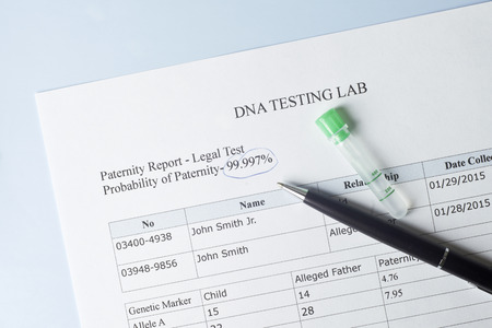 Paternity test results with pen and lab sample.