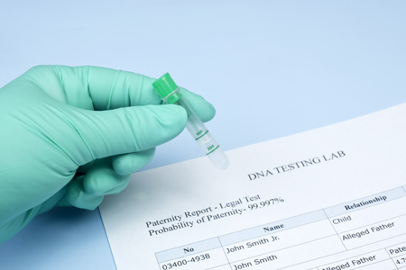Paternity test results with technician holding lab sample. Archivio Fotografico