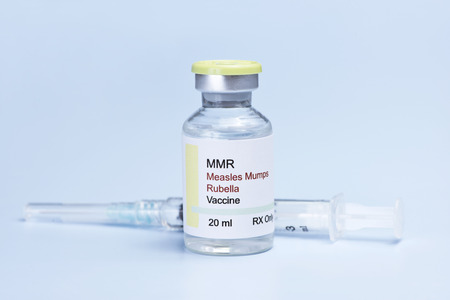 Measles, mumps, rubella, virus vaccine and syringe on blue background.