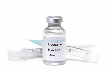 Glass vial of lidocaine injection solution with syringe on white. Standard-Bild