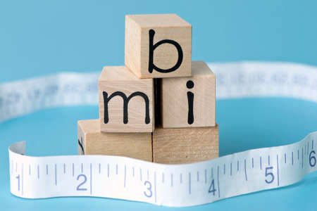 bmi: BMI body mass index letter blocks with tape measure.