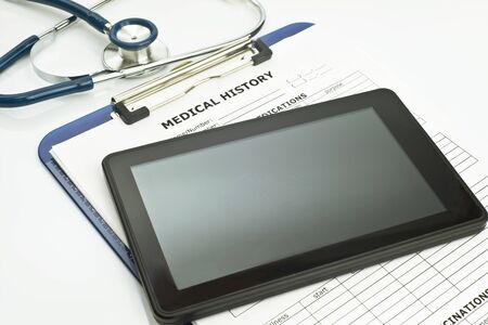 computing device: Personal computing device with stethoscope and patient medical record. Stock Photo