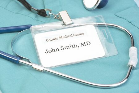 fictitious: Obviously fictitious Doctor identification tag on scrubs with stethoscope.