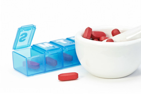morter: Rred tablets with mortar and pestle and blue daily medication dispenser.
