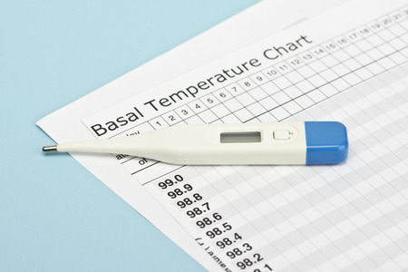 Basal temperature chart with thermometer to predict ovulation.