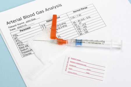 blood draw: Arterial blood gas sample syringe with name tag and laboratory report.  Heparin is a common non-trademarked medication name. Stock Photo