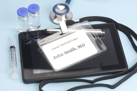 computing device: Obviously fictitious Doctor identification tag on personal computing device with stethoscope and vials.