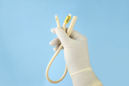 Close up view of nurse holding urinary catheter prior to use.