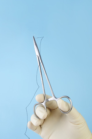 Surgeon holding surgical needle holder with silk suture on blue.