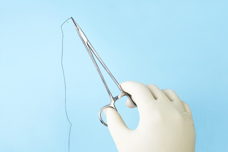 Surgeon holding surgical needle holder with silk suture on blue. Zdjęcie Seryjne - 40260791