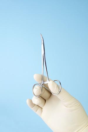 surgical: Cirujano celebración pequeñas pinzas hemostáticas curvas sobre fondo azul. Foto de archivo