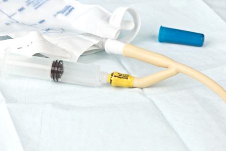 Nurse inflates urinary catheter bulb with leg drainage bag on sterile field. Standard-Bild