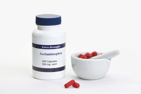 pestle: Acetaminophen bottle with two red tablets and mortar and pestle.