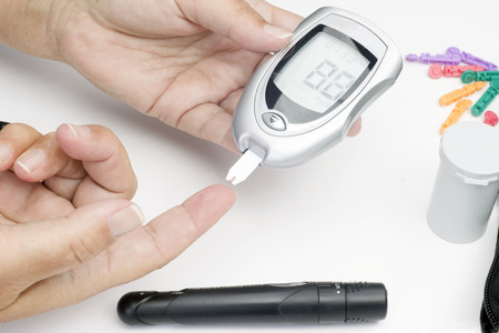 prick: Diabetic patient tests blood for glucose level.