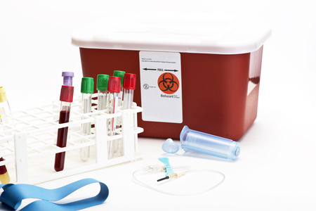 Blood collection tubes in tube rack with blue butterfly catheter and sharps container.