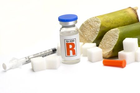 mellitus: Sugar cubes, sugarcane, and insulin bottle with syringe. Stock Photo