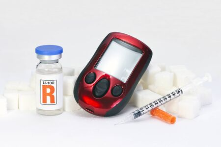 insulin bottle: Glucometer with sugar cubes, insulin bottle and syringe. Stock Photo