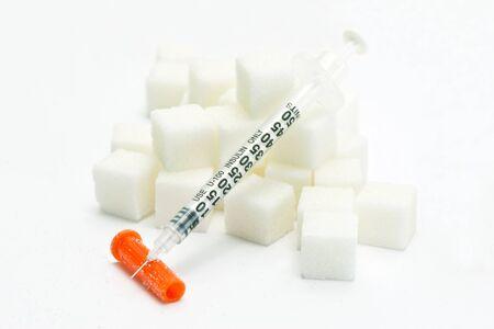 Diabetes insulin syringe with white sugar cubes. Stock fotó