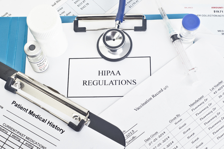 Hipaa regulations manual with patient documents.  All labels and/or documents are fictitious.  Names, serial numbers, and/or dates, are random and any resemblance to actual products is purely cooincidental. Foto de archivo