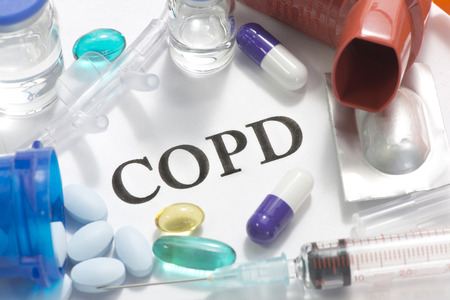 COPD concept photo with nasal cannula, pills, vials, and syringe.