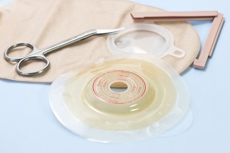 Ostomy supplies with scissors on blue background. 写真素材