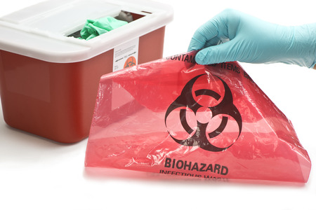 Health care worker's gloved hand with hazardous waste container and bag.