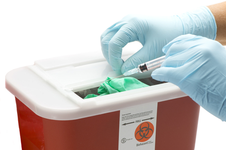 Health care worker's gloved hand drops syringe into hazardous waste container.
