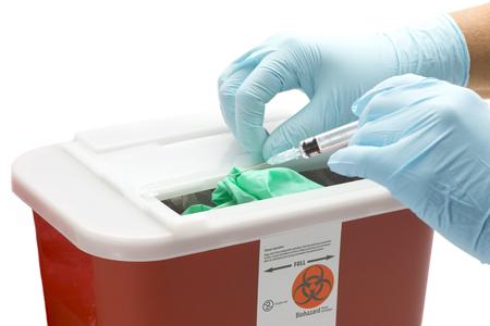 La mano enguantada de trabajador de la salud cae jeringa en contenedor de desechos peligrosos. Foto de archivo - 55064658