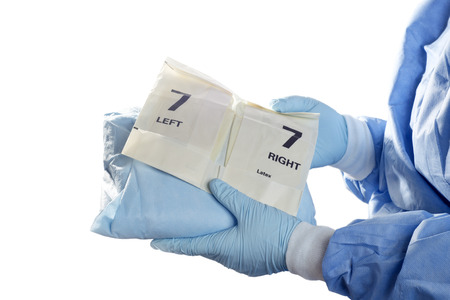 white glove: Operating room technician holds gown and gloves for surgeon. Stock Photo